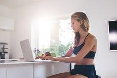 Bella donna che si siede dal contatore di cucina e che per mezzo del computer portatile Fotografia Stock Libera da Diritti
