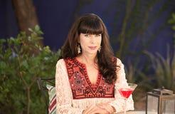 Bella donna che si siede fuori con la bevanda rossa fotografia stock libera da diritti