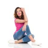 Bella donna che si siede su un pavimento Fotografie Stock
