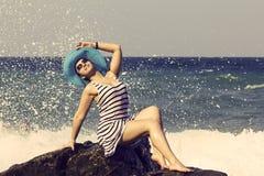 Bella donna che si siede su una pietra e su una spruzzatura Fotografia Stock