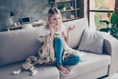 Bella donna che si siede sul sofà nel suo salone che ha tessuto immagini stock