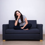 Bella donna che si siede sul sofà e che pensa a qualcosa Immagini Stock Libere da Diritti