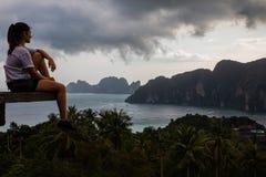 Bella donna che si siede sulla piattaforma di legno con le viste dell'isola di Phi Phi ed il cielo nuvoloso fotografie stock