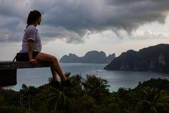 Bella donna che si siede sulla piattaforma di legno con le viste dell'isola di Phi Phi ed il cielo nuvoloso fotografia stock libera da diritti