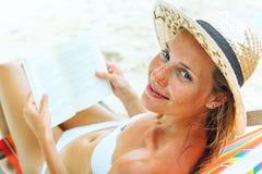 Bella donna che si siede sulla spiaggia che legge un libro Immagine Stock Libera da Diritti