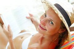 Bella donna che si siede sulla spiaggia che legge un libro Immagini Stock Libere da Diritti