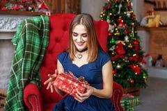 Bella donna che si siede in una poltrona e che si rallegra un regalo con Fotografie Stock