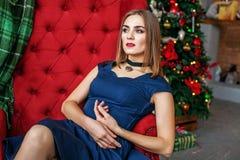 Bella donna che si siede in una poltrona vicino ad un albero di abete Concetto Fotografia Stock Libera da Diritti
