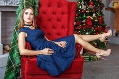 Bella donna che si siede in una poltrona vicino ad un albero di abete Sho del tallone Fotografia Stock
