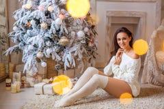 Bella donna che si siede vicino all'albero di Natale sul pavimento in un maglione bianco e nelle ghette bianche fotografia stock