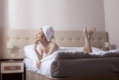 Bella donna che si trova a letto dopo la presa della doccia immagini stock libere da diritti