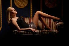 Bella donna che si trova su un sofà di cuoio fotografia stock libera da diritti