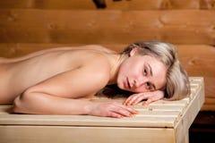 Bella donna che si trova sul letto di legno della stazione termale, riposando, rilassarsi, preparante per il massaggio Immagine Stock Libera da Diritti