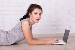Bella donna che si trova sul pavimento e che per mezzo del computer portatile Immagini Stock Libere da Diritti
