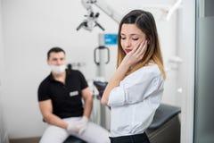 Bella donna che soffre dal dolore di denti terribile, guancia commovente con la mano alla clinica dentaria fotografia stock