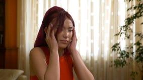Bella donna che soffre dalle mani dello sfregamento di emicrania contro le tempie video d archivio