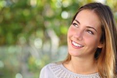Bella donna che sorride con denti perfetti e che guarda sopra Immagini Stock