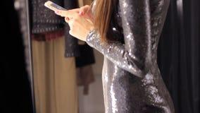 Bella donna che sorride facendo uso dello Smart Phone alla divisione sociale d'uso di media del vestito da modo dell'oro del part stock footage
