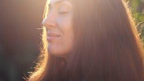 Bella donna che sorride nei raggi del sole di tramonto Primo piano del fronte L'umore, piacere, rilassamento, si rilassa archivi video