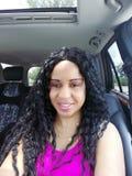 Bella donna che sorride in ritratto dell'automobile con il bambino Seat nella parte posteriore fotografia stock