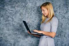 Bella donna che sta con il computer portatile fotografie stock
