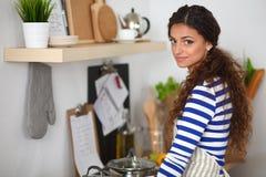 Bella donna che sta nella cucina con il grembiule fotografia stock libera da diritti