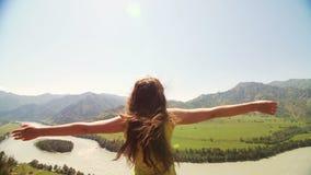 Bella donna che sta sopra la montagna e che allunga fuori le mani stock footage