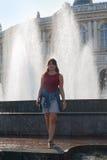 Bella donna che sta vicino alla fontana fotografie stock libere da diritti