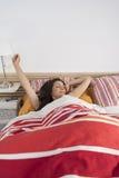 Bella donna che sveglia e che allunga nel letto rosso e giallo Immagine Stock