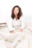 Bella donna che sveglia nel suo letto nella camera da letto Immagine Stock