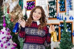 Bella donna che tiene i piccoli sacchetti della spesa dentro Immagini Stock
