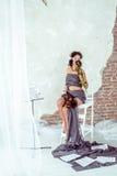 Bella donna che tiene un violino e che odora rosa rossa fotografia stock libera da diritti
