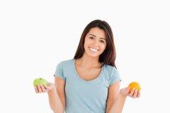 Bella donna che tiene una mela e un arancio Fotografia Stock Libera da Diritti