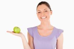 Bella donna che tiene una mela mentre levandosi in piedi Fotografie Stock