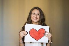 Bella donna che tiene una pace di carta con cuore rosso Fotografie Stock