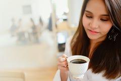 Bella donna che tiene una tazza di caffè in sua mano nella caffetteria del fondo della sfuocatura con lo spazio della copia per t Fotografie Stock Libere da Diritti