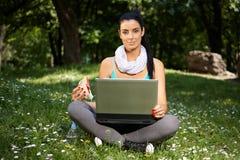 Bella donna che utilizza computer portatile nella sosta Fotografia Stock Libera da Diritti