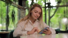 Bella donna che utilizza smartphone nel caffè di estate