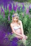 Bella donna circondata dal giacimento di fiori Fotografia Stock Libera da Diritti