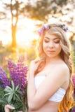 Bella donna circondata dal giacimento di fiori Fotografia Stock