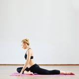 Bella donna con alta flessibilità del corpo che si esercita nella palestra Fotografie Stock