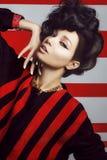 Bella donna con capelli ricci su un rosso bianco a strisce Fotografie Stock
