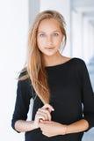 Bella donna con gli occhi azzurri in una camicia nera su un backg leggero immagine stock