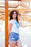 Bella donna con gli occhiali da sole ed il cappello alla moda del sole che prende il sole sulla sedia di salotto vicino alla pisc Fotografia Stock