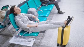 Bella donna con i brevi capelli castana che si trovano nell'sedili con le sue gambe su un bagaglio archivi video