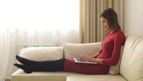 Bella donna con i capelli di scarsità che si siedono sul sofà nella stanza e che sorridono facendo uso del computer portatile video d archivio