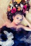 Bella donna con i fiori in suoi capelli su fondo dorato Fotografia Stock