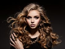 Bella donna con i gioielli lunghi dell'oro e dei capelli ricci Immagine Stock Libera da Diritti