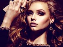 Bella donna con i gioielli lunghi dell'oro e dei capelli ricci Fotografia Stock Libera da Diritti