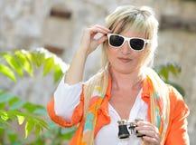 Bella donna con il binocolo ed i vetri di sole Fotografia Stock Libera da Diritti
